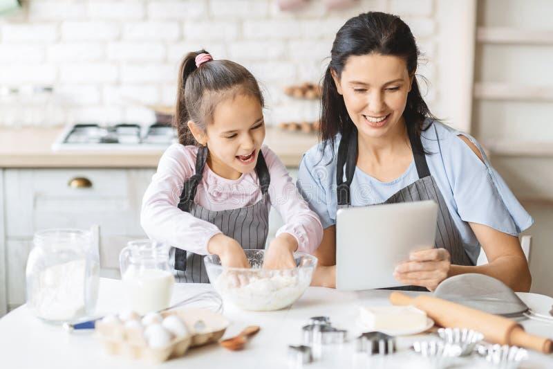 Moeder en dochter die digitale tablet in de keuken gebruikt, op zoek naar recept royalty-vrije stock foto's