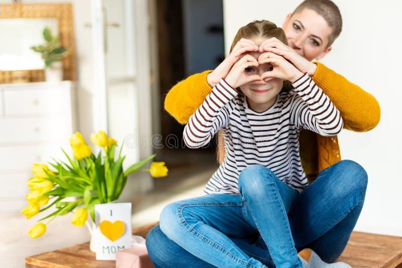 Moeder en dochter die door hart gestalte gegeven de handgebaar van het liefdesymbool kijken Familie, liefde, samenhorigheidsconce stock fotografie