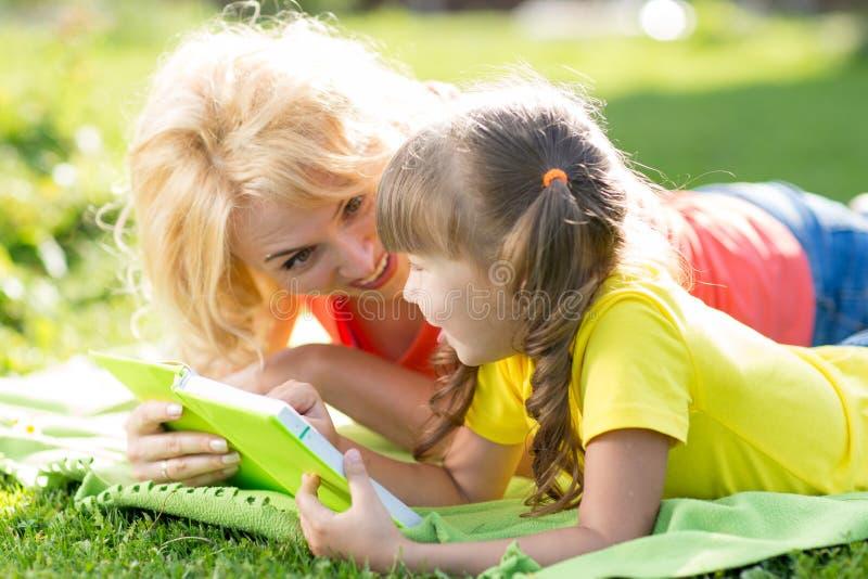 Moeder en dochter die een boek lezen bij het park stock afbeeldingen