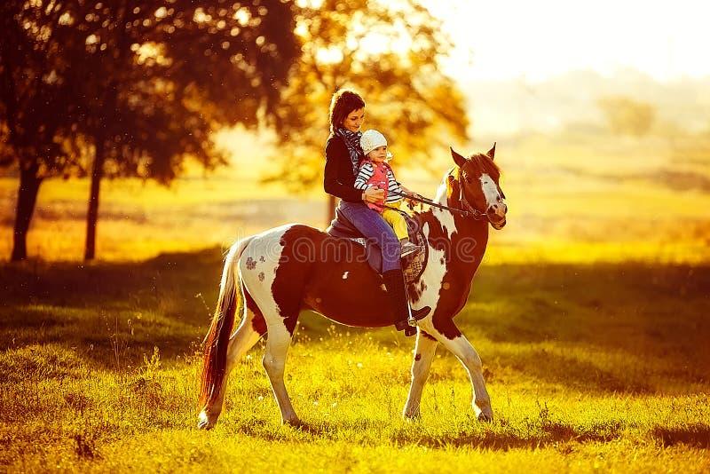 Moeder en dochter die een paard berijden stock foto