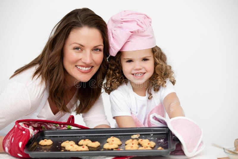 Moeder en dochter die een plaat met koekjes houden stock foto's