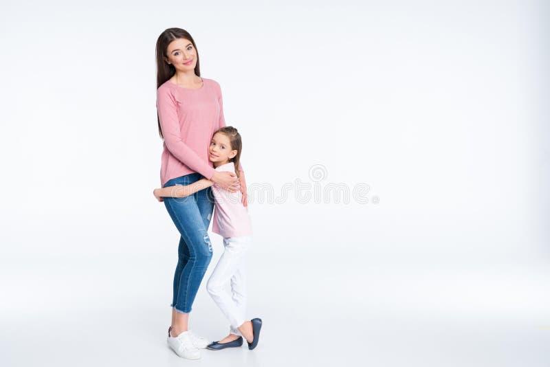 Moeder en dochter die en bij camera op wit koesteren glimlachen royalty-vrije stock afbeelding