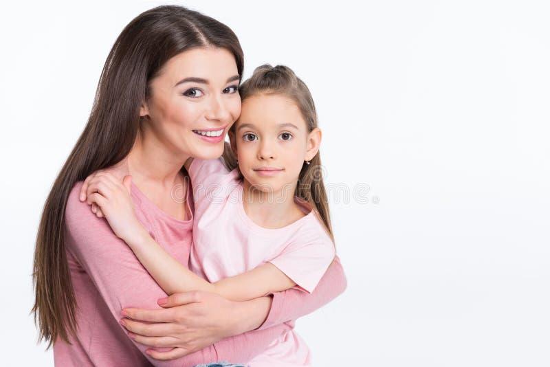 Moeder en dochter die en bij camera op wit koesteren glimlachen stock fotografie