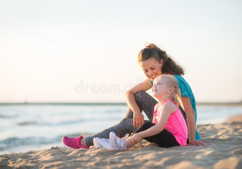 Moeder en dochter die en op het strand spreken zitten stock foto