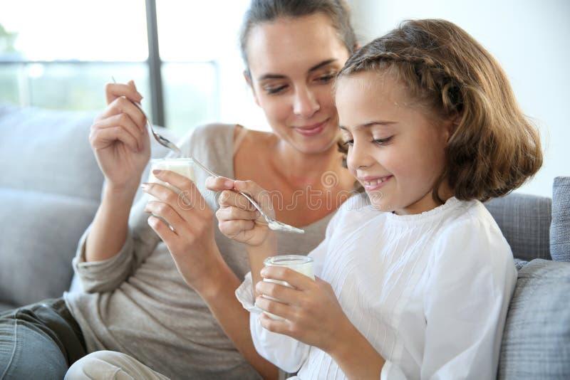 Moeder en dochter die etend yoghurt genieten van stock afbeeldingen
