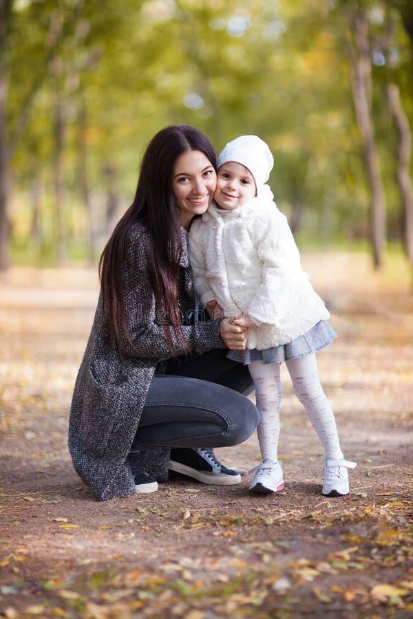 Moeder en dochter die in het de herfstpark lopen De scène van de schoonheidsaard met kleurrijke achtergrond, gele bomen en blader royalty-vrije stock foto's