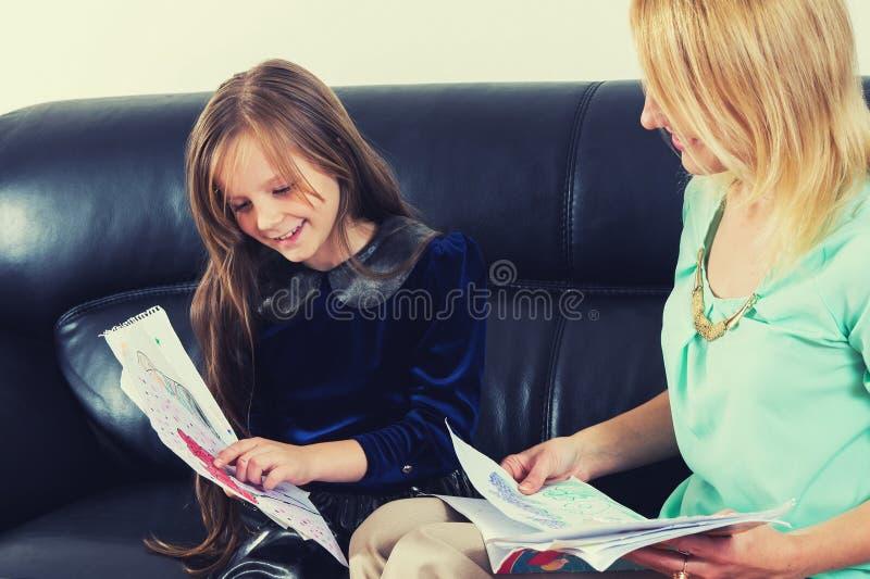 Moeder en dochter die het thuiswerk doen stock fotografie