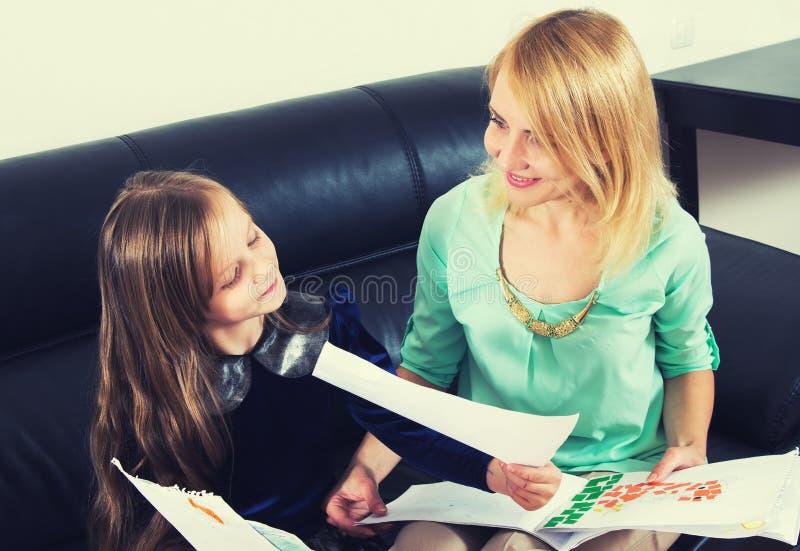 Moeder en dochter die het thuiswerk doen royalty-vrije stock afbeeldingen