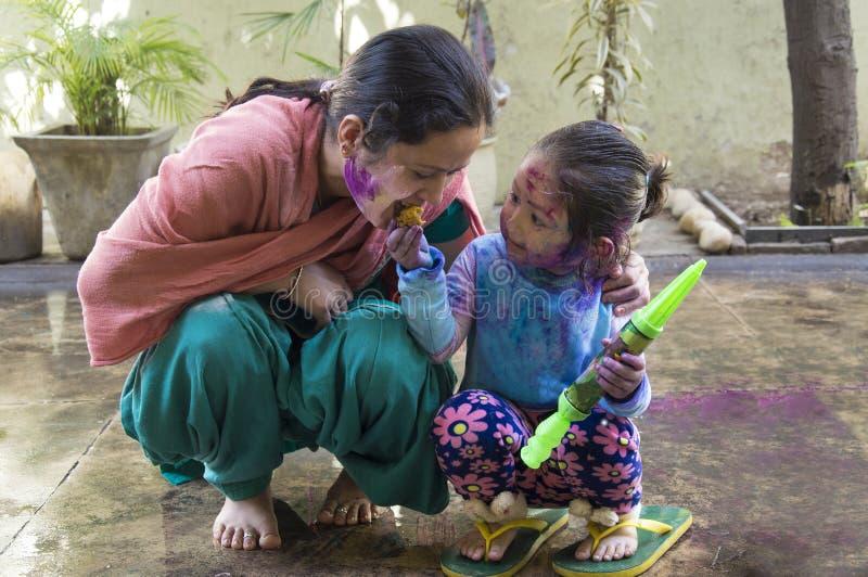 Moeder en dochter die Holi, het festival vieren van kleuren stock fotografie