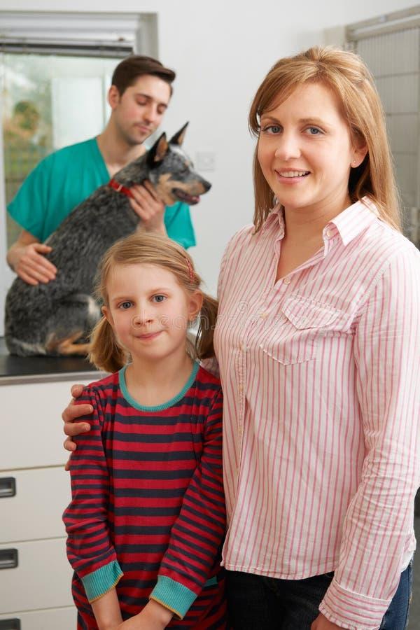 Moeder en Dochter die Hond voor Onderzoek nemen bij Dierenartsen royalty-vrije stock foto's