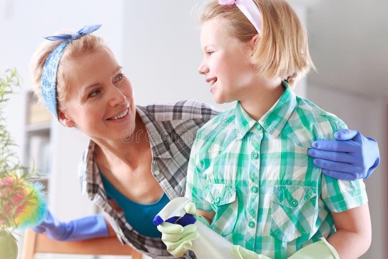 Moeder en dochter die hun huis schoonmaken stock afbeelding