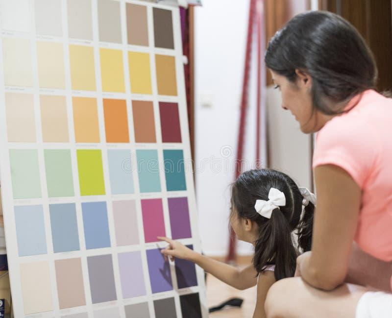 Moeder en dochter die kleuren voor verfslaapkamer kiezen royalty-vrije stock afbeeldingen