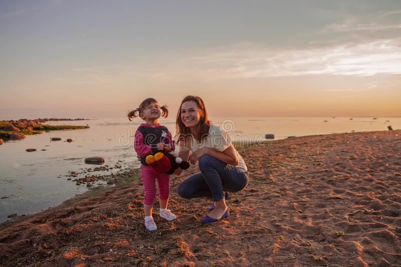 Moeder en dochter die langs het strand bij zonsondergang lopen Het concept een gelukkige vriendschappelijke familie stock foto