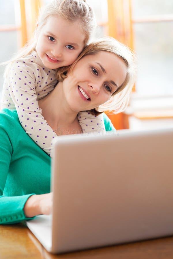 Moeder en dochter die laptop met behulp van stock foto