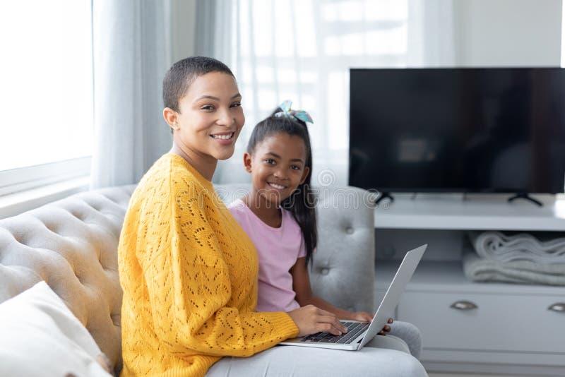 Moeder en dochter die laptop op een bank in woonkamer met behulp van royalty-vrije stock afbeelding