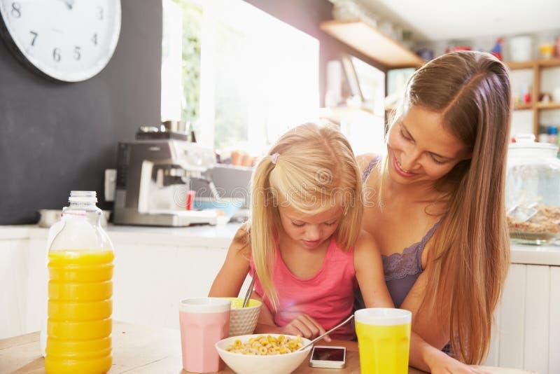 Moeder en Dochter die Mobiele Telefoon met behulp van bij Ontbijtlijst stock afbeeldingen