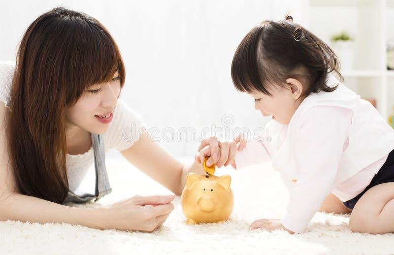 Moeder en dochter die muntstukken zetten in spaarvarken royalty-vrije stock fotografie