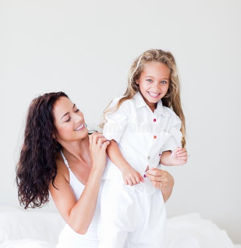 Moeder en dochter die op bed bij camera glimlachen stock fotografie