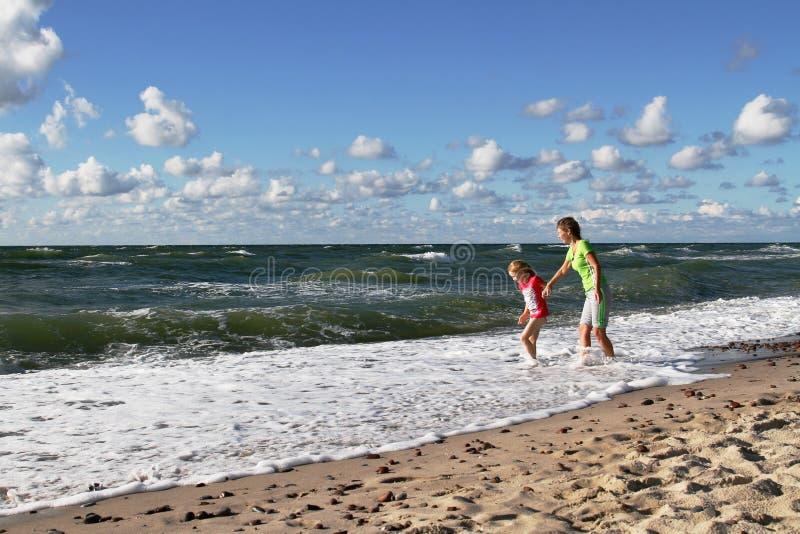 Moeder en dochter die op de kust van de Oostzee lopen stock afbeelding