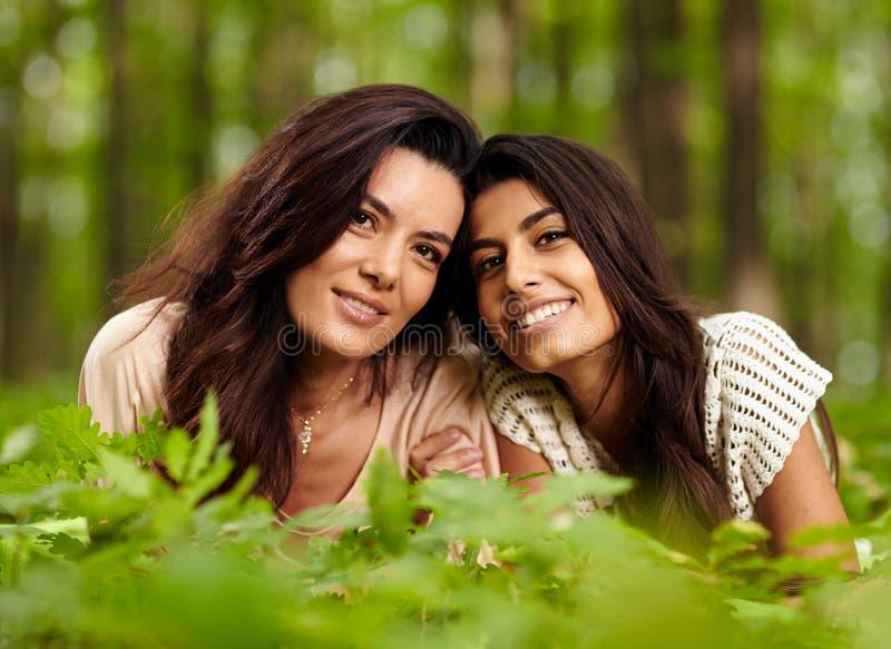 Moeder en dochter die op deken bij een picknick leggen royalty-vrije stock fotografie