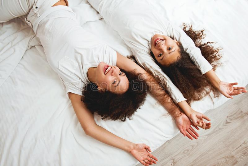 Moeder en dochter die op het bed genieten van, gelukkig, het glimlachen royalty-vrije stock foto's