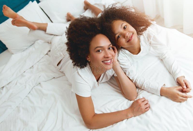 Moeder en dochter die op het bed genieten van, gelukkig, het glimlachen royalty-vrije stock fotografie