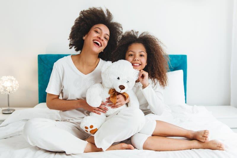 Moeder en dochter die op het bed genieten van, gelukkig, het glimlachen stock fotografie