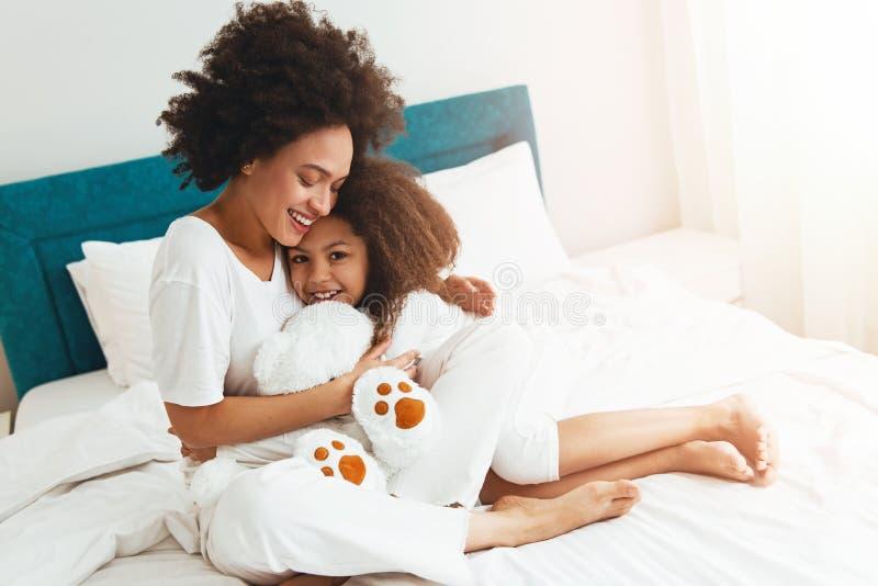 Moeder en dochter die op het bed genieten van, gelukkig, het glimlachen stock foto