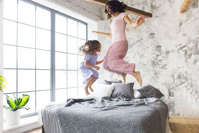 Moeder en dochter die op het bed springen stock fotografie
