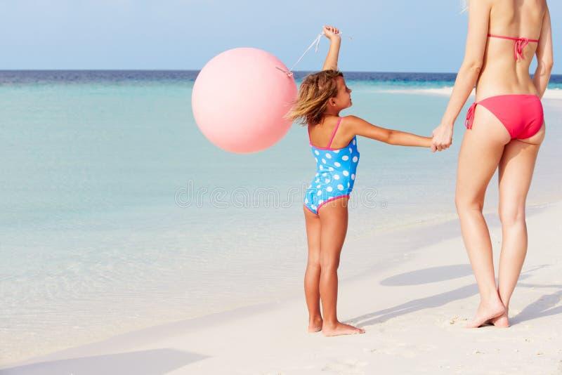 Moeder en Dochter die op Mooi Strand met Ballon lopen royalty-vrije stock afbeeldingen