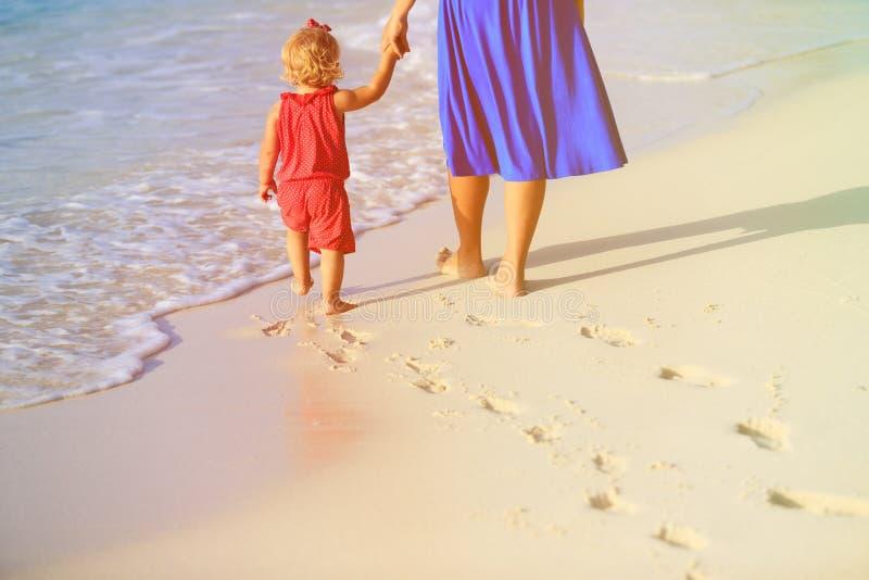 Moeder en dochter die op strand lopen die voetafdruk in zand verlaten stock foto