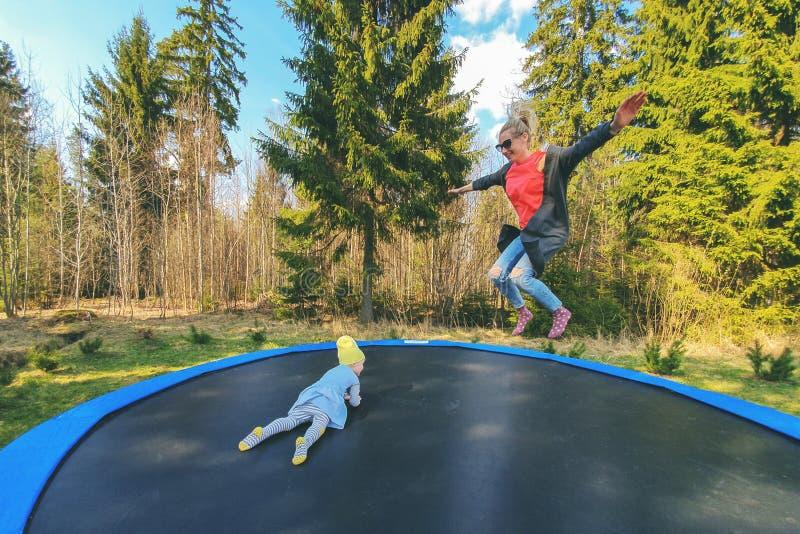 Moeder en dochter die op trampoline in openlucht springen stock afbeeldingen