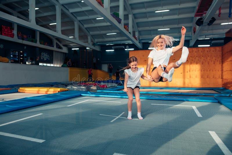 Moeder en dochter die op trampoline springen en spleet doen stock foto's