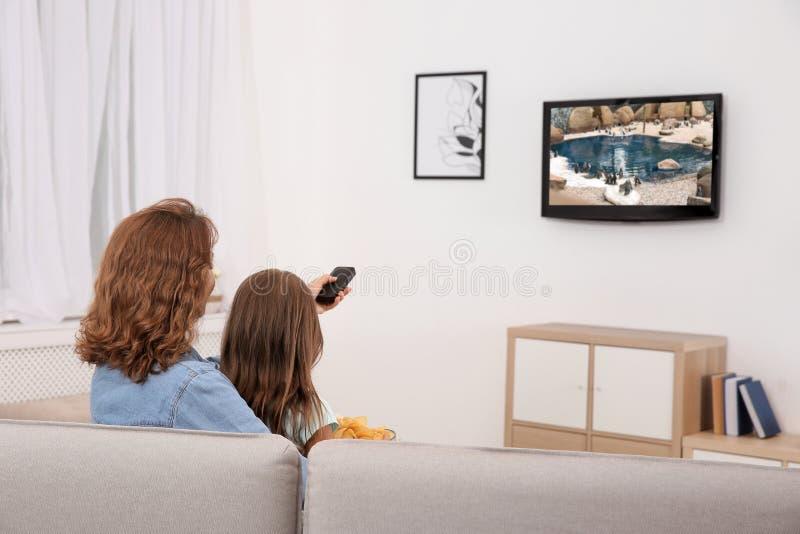 Moeder en dochter die op TV op bank letten royalty-vrije stock foto