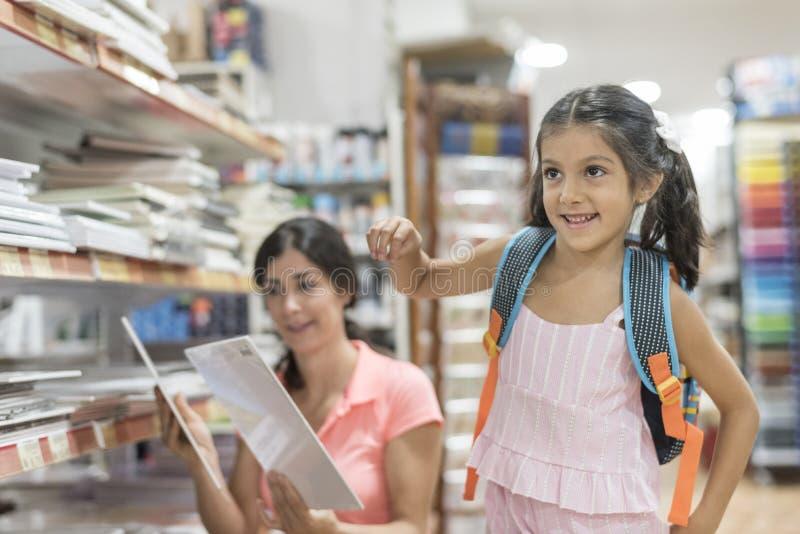 Moeder en dochter die in opslag materiaal voor terug naar school kiezen stock afbeeldingen