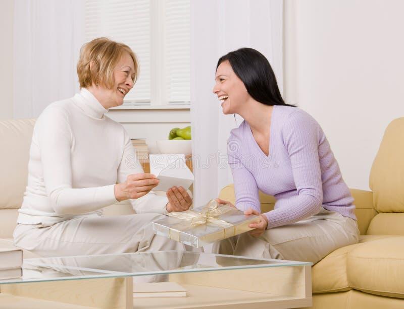 Moeder en dochter die over gift lachen royalty-vrije stock afbeeldingen