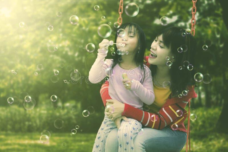 Moeder en dochter die pret blazende zeepbels hebben bij park stock fotografie