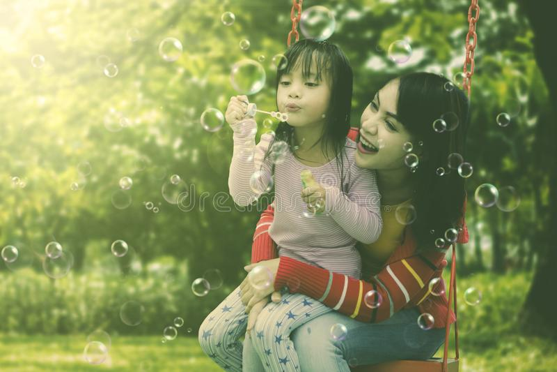 Moeder en dochter die pret blazende zeepbels hebben bij park stock afbeeldingen