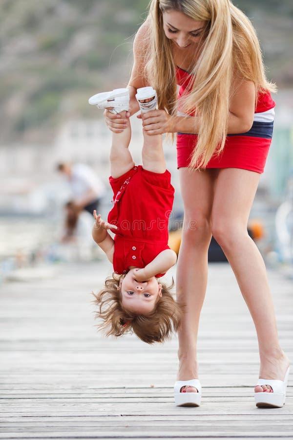Moeder en dochter die pret buiten op het dok hebben stock afbeelding