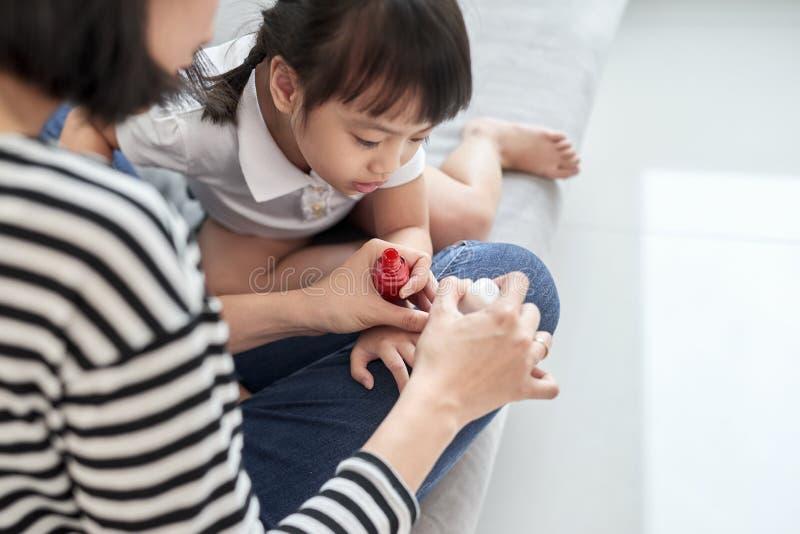 Moeder en dochter die pret het schilderen vingernagels, het concept van de familietijd hebben royalty-vrije stock fotografie