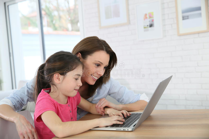 Moeder en dochter die pret het websurfing op laptop hebben stock afbeelding