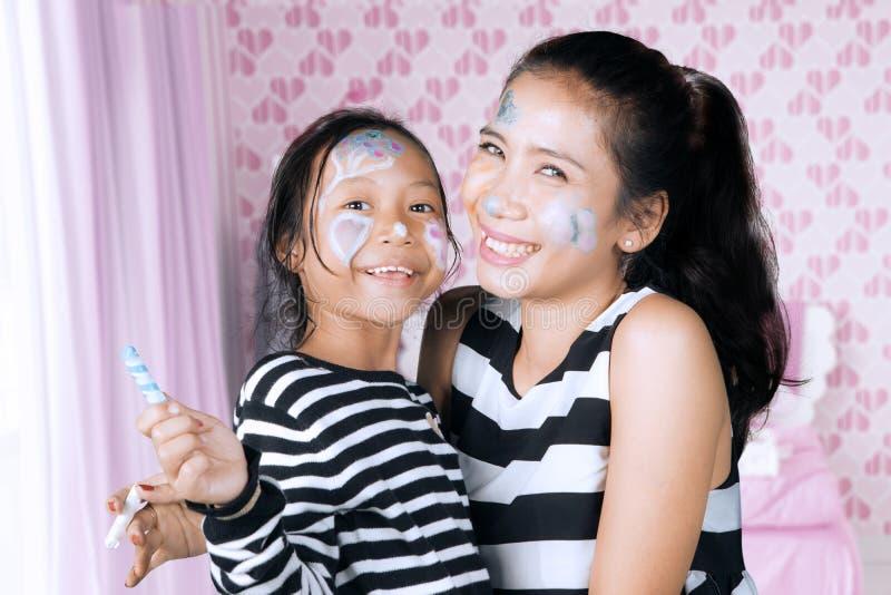 Moeder en dochter die pret met gezicht het schilderen hebben stock foto