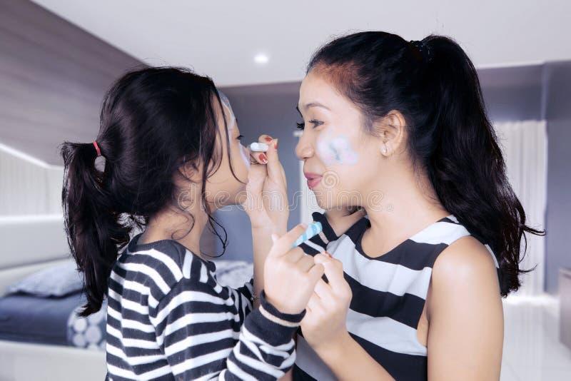 Moeder en dochter die pret met gezicht het schilderen hebben stock afbeeldingen