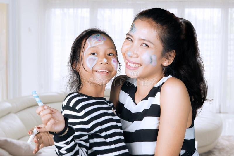 Moeder en dochter die pret met gezicht het schilderen hebben royalty-vrije stock afbeelding