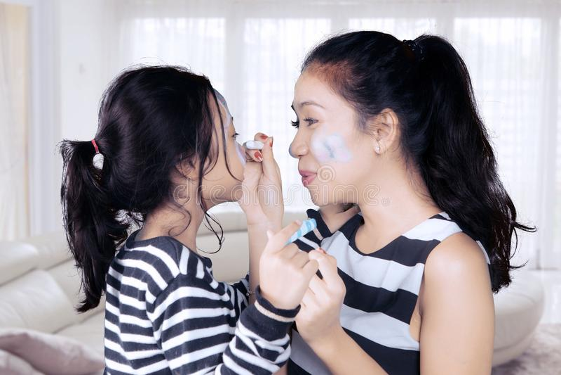 Moeder en dochter die pret met gezicht het schilderen hebben royalty-vrije stock foto