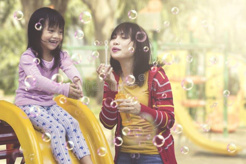 Moeder en dochter die pret met zeepbels hebben bij speelplaats stock foto