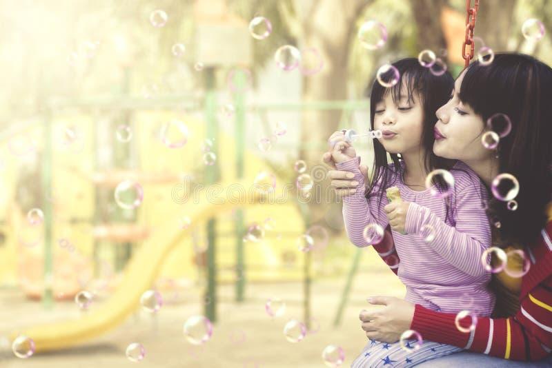 Moeder en dochter die pret met zeepbels hebben bij speelplaats royalty-vrije stock foto