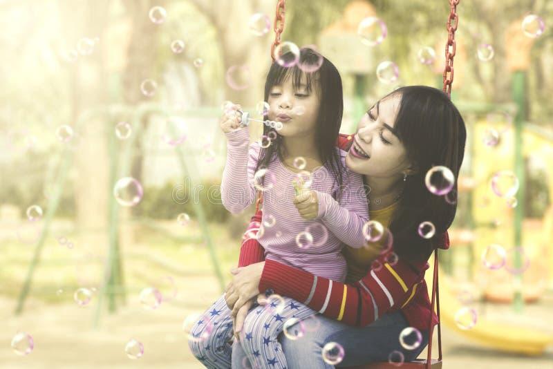 Moeder en dochter die pret met zeepbels hebben bij speelplaats stock fotografie