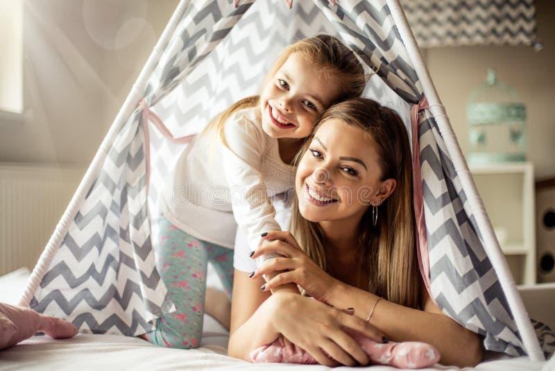 Moeder en dochter die pret in tipi hebben royalty-vrije stock afbeelding