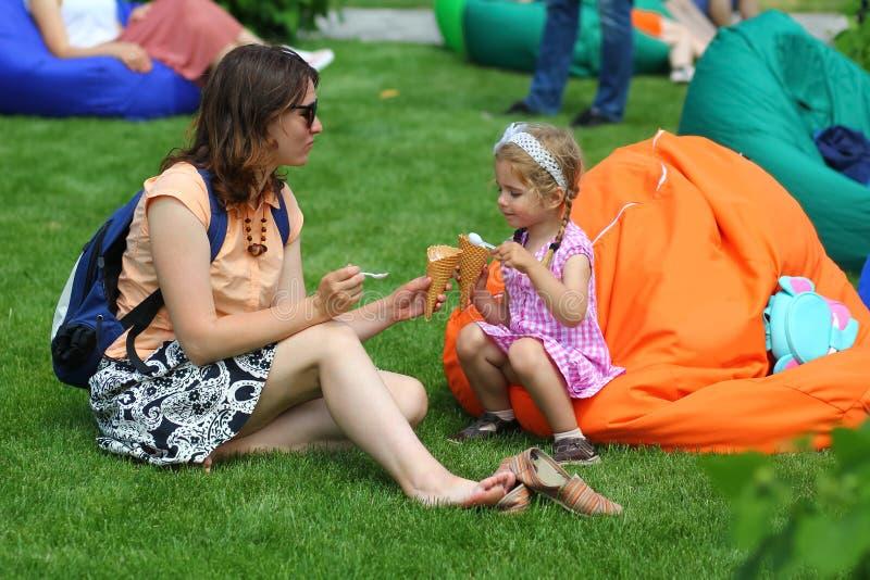 Moeder en dochter die roomijs in het de zomerpark eten royalty-vrije stock fotografie